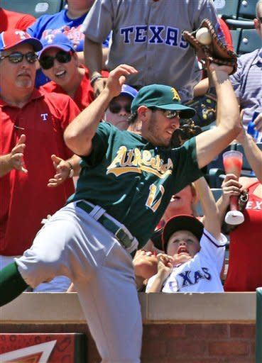 Fans react as Oakland Athletics first baseman Adam Rosales (17) catches a pop-fly in foul territory hit by Texas Rangers' Ian Kinsler during the first inning of a baseball game, Thursday, May 17, 2012, in Arlington, Texas. (AP Photo/LM Otero)