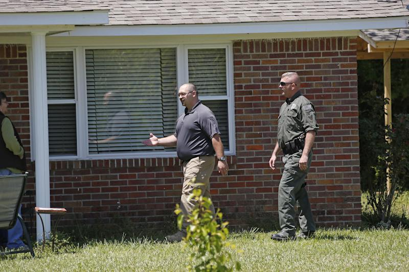 Itawamba County Sheriff's Department deputies finish inspecting a home and property in the Ozark community, northeast of Tupelo, Miss., Thursday, April 25, 2013. The officers were looking for Everett Dutschke, a person of interest in connection with the investigation into the recent ricin-laced letters mailed to President Barack Obama and others. No charges have been filed against Dutschke and he hasn't been arrested. (AP Photo/Rogelio V. Solis)