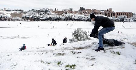 A man prepares to slide with a plastic bag during a heavy snowfall, at the Circus Maximus, in Rome, Italy February 26, 2018. REUTERS/Yara Nardi