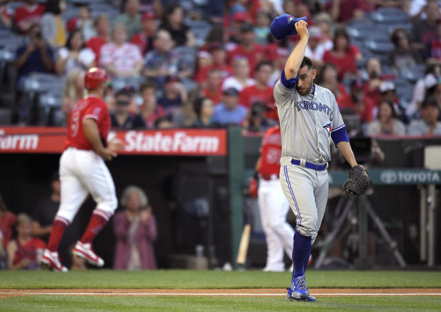 Toronto Blue Jays starting pitcher Marco Estrada, right, wipes his face after Los Angeles Angels' Albert Pujols, left, scored on a single by Luis Valbuena during the first inning of a baseball game Friday, June 22, 2018, in Anaheim, Calif. (AP Photo/Mark J. Terrill)