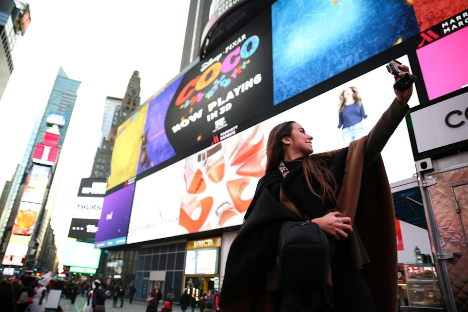 A tourist takes a selfie picture at Times Square. REUTERS/Amr Alfiky