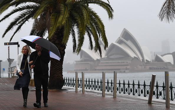 A couple walk under an umbrella beside the harbour with the Opera House in the background in Sydney, Australia.