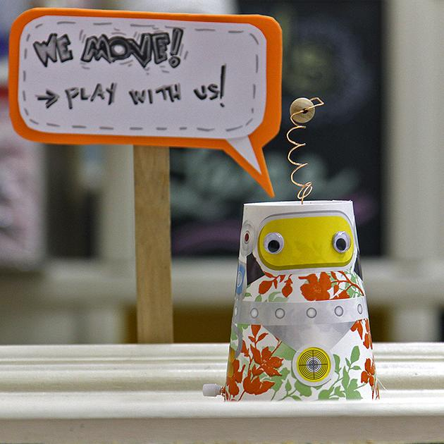 A little paper cup robot greets visitors at the entrance of the workshop.