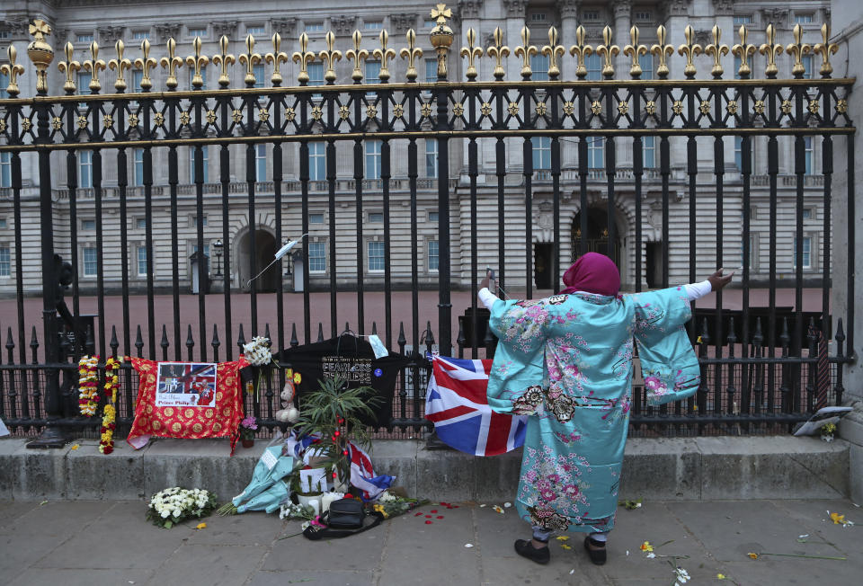 A woman gestures as she sings next to tributes left in honor of Britain's Prince Philip in front of Buckingham Palace in London on Saturday, April 10, 2021. Prince Philip, the irascible and tough-minded husband of Queen Elizabeth II who spent more than seven decades supporting his wife in a role that both defined and constricted his life, has died, Buckingham Palace said Friday. He was 99. (AP Photo/Tony Hicks)