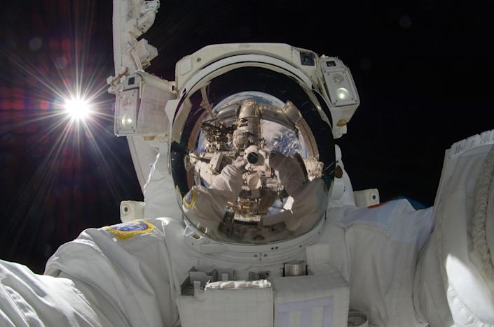 """File - In this Sept. 5, 2012, file photo, provided by NASA, Japan Aerospace Exploration Agency astronaut Aki Hoshide, Expedition 32 flight engineer, uses a digital still camera to expose a photo of his helmet visor during the mission's third session of extravehicular activity (EVA). During the six-hour, 28-minute spacewalk, Hoshide and NASA astronaut Sunita Williams (visible in the reflections of Hoshide's helmet visor), flight engineer, installed a camera on the International Space Station's robotic arm, Canadarm2. """"Selfie"""" the smartphone self-portrait has been declared word of the year for 2013 by Britain's Oxford University Press. (AP Photo/Nasa, Aki Hoshide, File)"""