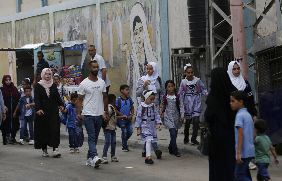 Women bring their children to the United-Nation run Elementary School on the first day of the new school year at the Shati refugee camp in Gaza City, Saturday, Aug. 8, 2020. Schools run by both Palestinian government and the U.N. Refugee and Works Agency (UNRWA) have opened almost normally in the Gaza Strip after five months in which no cases of community transmission of the coronavirus had been recorded. (AP Photo/Adel Hana)