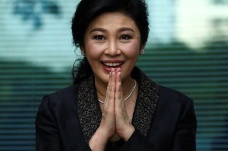 Ousted former Thai prime minister Yingluck Shinawatra greets supporters as she arrives at the Supreme Court in Bangkok