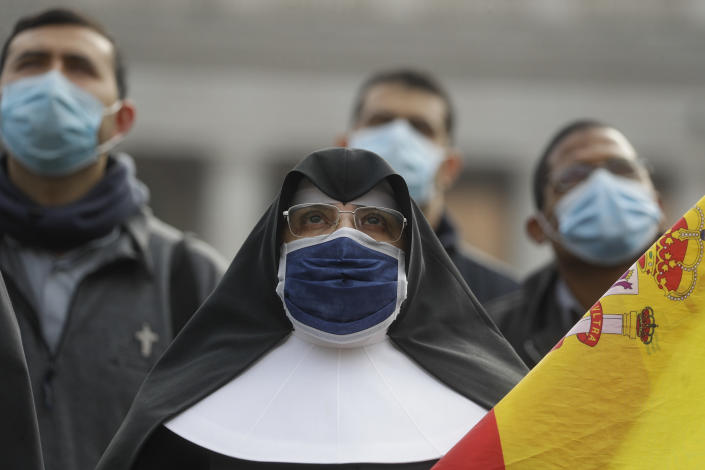 A nun wearing a face mask as she looks up at Pope Francis reciting the Angelus prayer from his studio window overlooking St.Peter's Square at the Vatican, Sunday, Nov. 29, 2020. Pope Francis, joined by the church's newest cardinals at Mass, has warned against mediocrity as well as promoting one's career rise. (AP Photo/Gregorio Borgia)