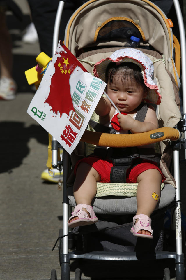 "A child holds a distorted Chinese national flag with a slogan ""Withdraw chinese patriotism classes"" on a stroller pushed by a parent during a march on a downtown street in Hong Kong Sunday, July 29, 2012, to protest the upcoming introduction in schools of Chinese patriotism classes that they fear will lead to brainwashing. Teachers, parents, students and pro-democracy activists marched Sunday to the government headquarters of the semiautonomous territory to protest against the new curriculum, which authorities are encouraging schools to begin using when classes resume in September. (AP Photo/Vincent Yu)"