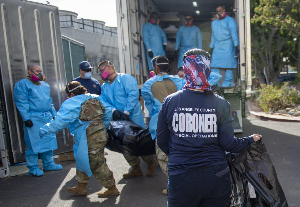 """FILE - In this Tuesday, Jan. 12, 2021, file photo, provided by the LA County Dept. of Medical Examiner-Coroner, Elizabeth """"Liz"""" Napoles, right, works alongside the National Guard who are helping to process COVID-19 deaths that are be placed into temporary storage at LA County Medical Examiner-Coroner Office in Los Angeles. Just a little more than a year after California announced its first case of coronavirus, the nation's most populous state is on the brink of recording its 40,000th death. (LA County Dept. of Medical Examiner-Coroner via AP, File)"""
