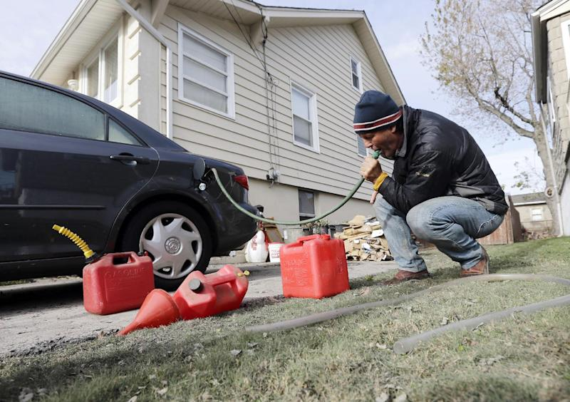 Chris Zaturoski uses a garden hose to attempt to siphon gasoline from his car to use in a generator at his house which is without power in the wake of superstorm Sandy on Thursday, Nov. 1, 2012, in Little Ferry, N.J. The hose was too big to fit into the gas tank of the car. New Jersey residents across the state were urged to conserve water. At least 1.7 million customers remained without electricity. (AP Photo/Mike Groll)