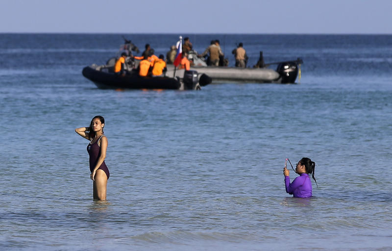 """A woman poses for a picture as security forces prepare for a drill at the country's most famous beach resort island of Boracay, in central Aklan province, Philippines Wednesday, April 25, 2018, a day before the government implements its temporary closure. Thousands of workers will be affected when Boracay will be closed after Philippine President Rodrigo Duterte orders its closure on April 26 for up to six months after saying the waters off its famed white-sand beaches had become a """"cesspool"""" due to overcrowding and development. (AP Photo/Aaron Favila)"""