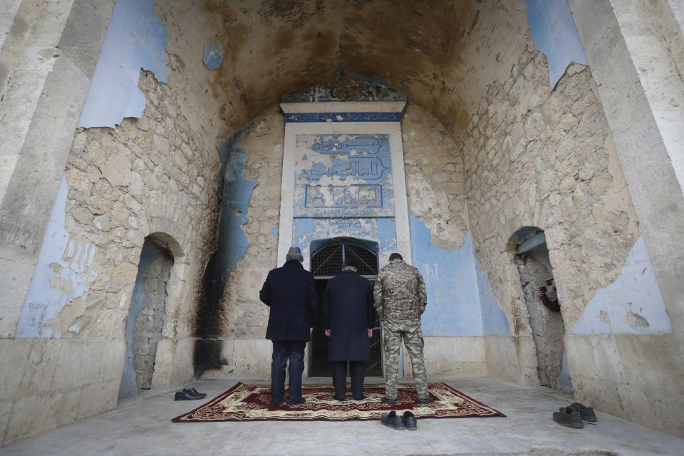 The Azerbaijanian religion officials and military officer pray in Mosque in Aghdam, after the Azerbaijani forces handed control that had been occupied by Armenian forces for a quarter-century, Aghdam, Azerbaijan, Friday, Nov. 20, 2020. Units of the Azerbaijani army on Friday morning entered the Aghdam region, a territory ceded by Armenian forces in a cease-fire agreement that ended six weeks of heavy fighting. (AP Photo/Sergei Grits)