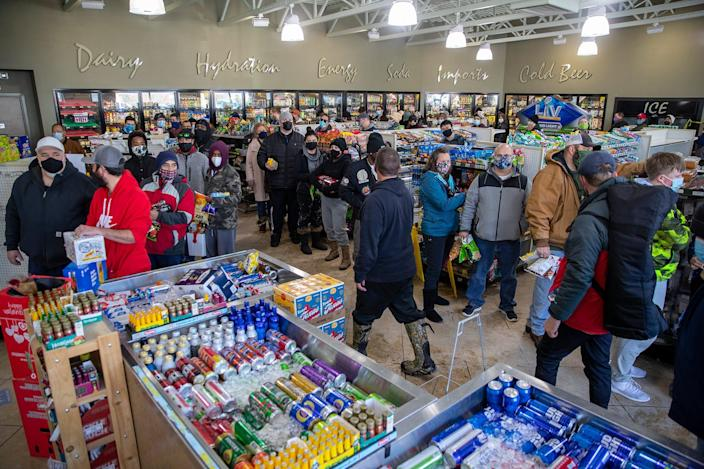 People wait in line to purchase food and snacks at a gas station in Pflugerville, Texas, on Tuesday, Feb 16, 2021. Most homes in the area were without power for nearly eight hours.