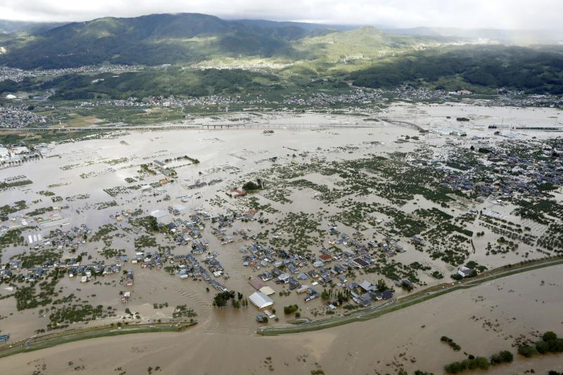 A residential area, center, is submerged in muddy waters after an embankment of the Chikuma River, bottom, broke because of Typhoon Hagibis, in Nagano, central Japan, Oct. 13, 2019. (Photo: Yohei Kanasashi/Kyodo News via AP)