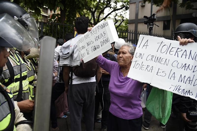 """Opposition activists confront riot police during the so-called """"march of the grand-parents"""" protest against the government in Caracas on May 12, 2017 (AFP Photo/JUAN BARRETO                        )"""