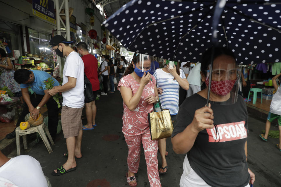 People wearing face masks buy food at a public market in preparation for stricter lockdown measures in Quezon city, Philippines on Monday, Aug. 3, 2020. (AP Photo/Aaron Favila)