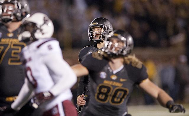 Missouri kicker Andrew Baggett, center, watches his field goal attempt hit the goalpost with teammates Sean Culkin, right, and Mitch Hall and South Carolina's Skai Moore during the second overtime of an NCAA college football game Saturday, Oct. 26, 2013, in Columbia, Mo. South Carolina won 27-24. (AP Photo/L.G. Patterson)