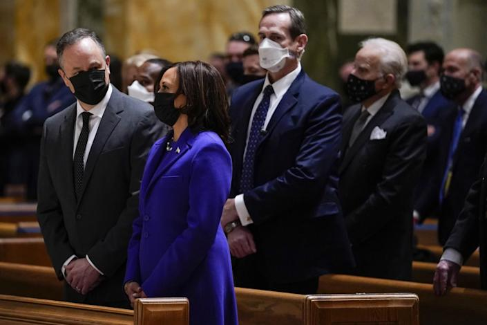 Kamala Harris and her husband, Doug Emhoff, stand in a pew at Mass at the Cathedral of St. Matthew the Apostle.