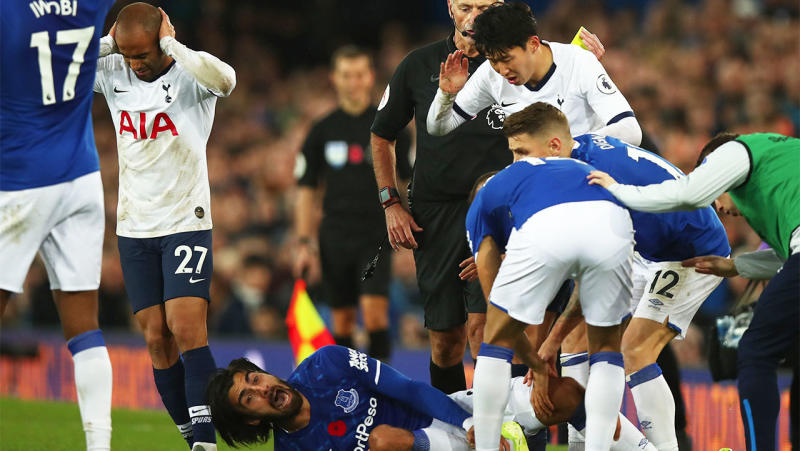 Son Heung-min looks on in horror with other players as Andre Gomes screams in pain after a tackle.