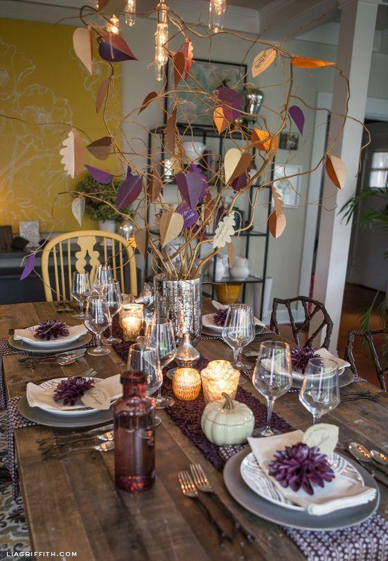"""<p>Photographer Lia Griffith used a woodland motif—note the natural wood, plum colored place cards, and twig-style silverware—to transform her dining room table into a beautiful natural scene. </p><p><strong>Get the tutorial at <a href=""""https://go.redirectingat.com?id=74968X1596630&url=http%3A%2F%2Fliagriffith.com%2Fthanksgiving-table-inspiration-editable-leaf-place-cards%2F&sref=https%3A%2F%2Fwww.countryliving.com%2Fentertaining%2Fg2130%2Fthanksgiving-centerpieces%2F"""" rel=""""nofollow noopener"""" target=""""_blank"""" data-ylk=""""slk:Lia Griffith"""" class=""""link rapid-noclick-resp"""">Lia Griffith</a>.</strong></p><p><strong><strong><a class=""""link rapid-noclick-resp"""" href=""""https://www.amazon.com/Elanze-Designs-Decorative-Pumpkins-Quantity/dp/B07CHVVC1S?tag=syn-yahoo-20&ascsubtag=%5Bartid%7C10050.g.2130%5Bsrc%7Cyahoo-us"""" rel=""""nofollow noopener"""" target=""""_blank"""" data-ylk=""""slk:SHOP FAUX WHITE PUMPKINS"""">SHOP FAUX WHITE PUMPKINS</a></strong><br></strong></p>"""