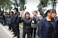 A woman cries as the coffin of retired local Communist Party chief Wu Renbao is driven through Huaxi village on March 22, 2013