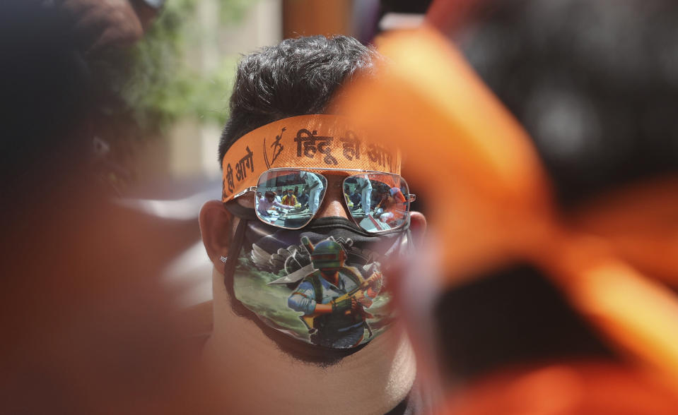 An activist of Rashtriya Bajrang Dal participates in a ceremony to mark the groundbreaking ceremony of a temple dedicated to the Hindu god Ram in Ayodhya, and the first anniversary of India's decision to revoke article 370, in Jammu, India, Wednesday, Aug 5, 2020. Despite the coronavirus restricting a large crowd, Hindus rejoiced as Indian Prime Minister Narendra Modi broke ground Wednesday on a long-awaited temple of their most revered god Ram at the site of a demolished 16th century mosque. Modi offered prayers to nine stone blocks with lord Ram inscribed on it amid chanting of Hindu religious hymns to symbolize the start of construction of the temple, which is expected to take three and a half years. (AP Photo/Channi Anand)