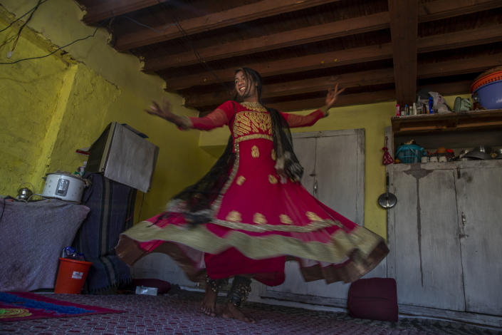 """A transgender Kashmiri Maliaka Sheikh, in tradition attire of Kashmiri dancers, poses for photographs inside the home of a friend on the outskirts of Srinagar, Indian controlled Kashmir, Thursday, June 3, 2021. The 22-year-old transgender left home as an 11-year-old and started living with other transgenders. """"At the beginning it was difficult for my family to understand me but fortunately, they have now accepted me for who I am,"""" Maliaka said. (AP Photo/ Dar Yasin)"""