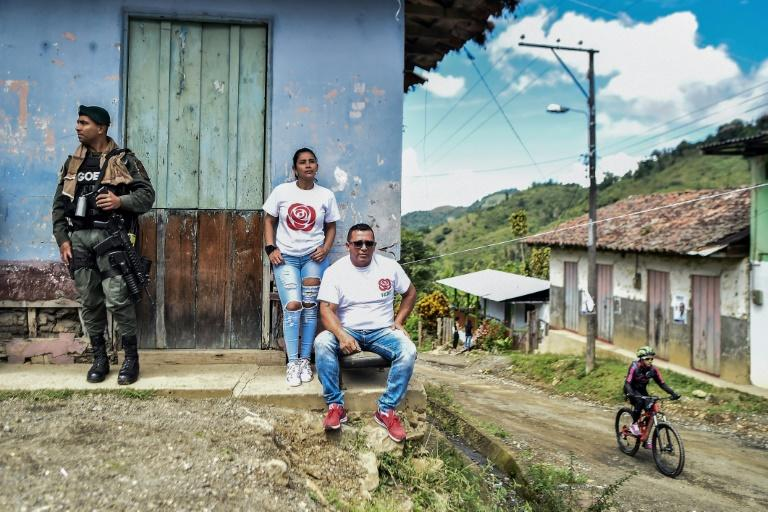 A police officer stands guards next to members of the political party formed by leftist FARC guerrillas under a 2016 peace accord, in Monteloro, Valle del Cauca Department, Colombia