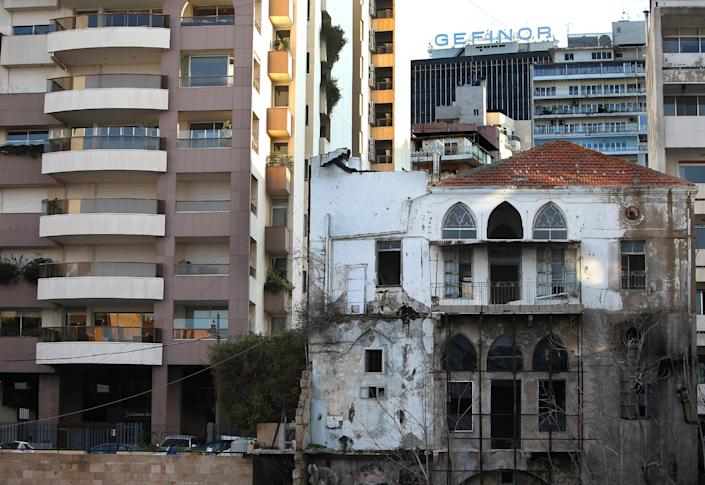 In this February 18, 2014 photo, an old abandoned building with a traditional red brick roof, right, is overshadowed by newly-built apartment buildings, in Beirut, Lebanon. One by one, the old traditional houses of Beirut are vanishing as luxury towers sprout up on every corner, altering the city's skyline almost beyond recognition amid an ongoing construction frenzy. While Lebanon's real estate sector has developed to become one of the country's success stories, many say it is coming at the expense of Lebanon's identity and heritage. (AP Photo/Hussein Malla)