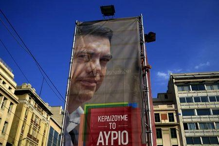 A worker hangs a banner with an image of former Greek prime minister and leader of leftist Syriza party Alexis Tsipras at the party's pre-election kiosk in Athens