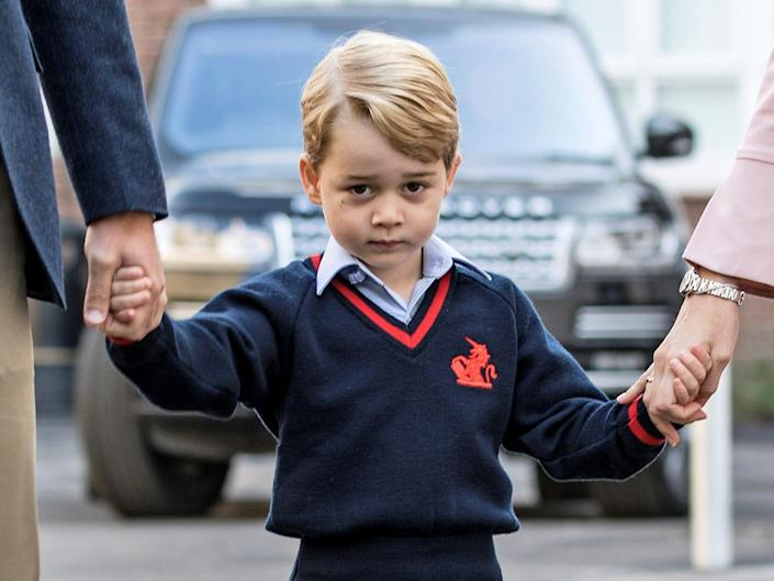 Prince George holds his parents' hands on his first day of school.