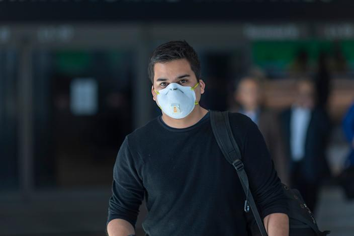 Travelers arrive at LAX airport wear face masks for protection against the coronavirus on February 2, 2020.