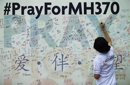 A woman writes a message on a board for family members of passengers onboard the missing Malaysia Airlines Flight MH370 at the MCA headquarters in Kuala Lumpur