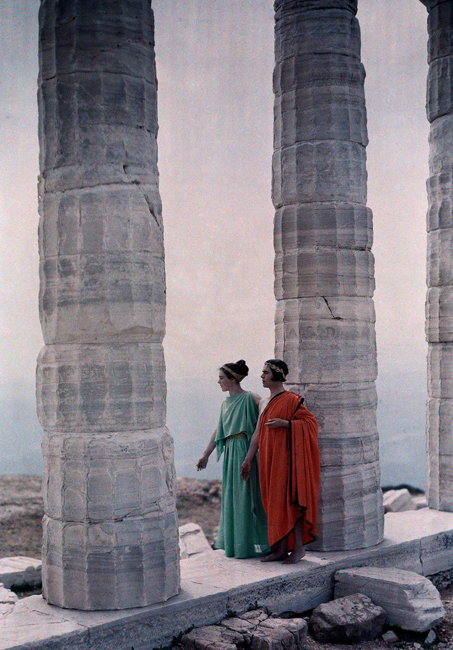 Two dancers in costume stand between the columns of Poseidon's Temple, Greece, 1930.