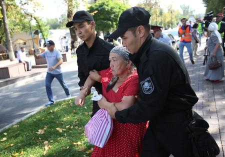 Law enforcement officers detain a woman during an anti-government protest in Almaty