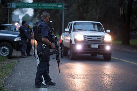 Police officers stand guard as they carry out inspections at a checkpoint after 13 people were killed in battles between rival gangs in two states in central and western Mexico, in Uruapan