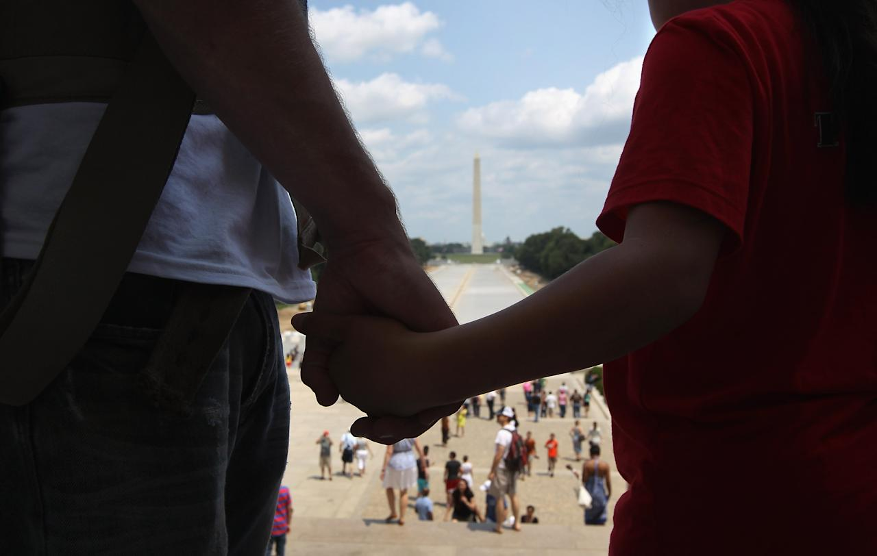 "A mentor holds hands with military chilld participating the the TAPS ""Good Grief Camp, while looking over the National Mall and the Washington Monument on May 26, 2012 in Washington, DC. Five hundred military children and teens, most of whom lost a parent or sibling in the Afghan and Iraq wars, are attending the four-day event in Arlington, Virginia and Washington, DC, which is run by TAPS (Tragedy Assistance Program for Survivors). The TAPS Good Grief Camp helps them learn coping skills and build relationships so they know they are not alone in the grief of their loved one. They meet others of their own age group, learn together and share their feelings, both through group activities and one-on-one mentors, who are all active duty or former military service members. Some 1,200 adults, most of whom are grieving parents and spouses, also attend the National Military Survival Seminar held concurrently with the children's camp. The TAPS slogan is ""Remember the Love. Celebrate the Life. Share the Journey.""  (Photo by John Moore/Getty Images)"