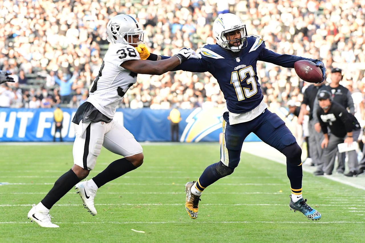<p>Keenan Allen #13 of the Los Angeles Chargers fends off T.J. Carrie #38 of the Oakland Raiders as Allen makes the catch during the third quarter of the game at StubHub Center on December 31, 2017 in Carson, California. (Photo by Harry How/Getty Images) </p>