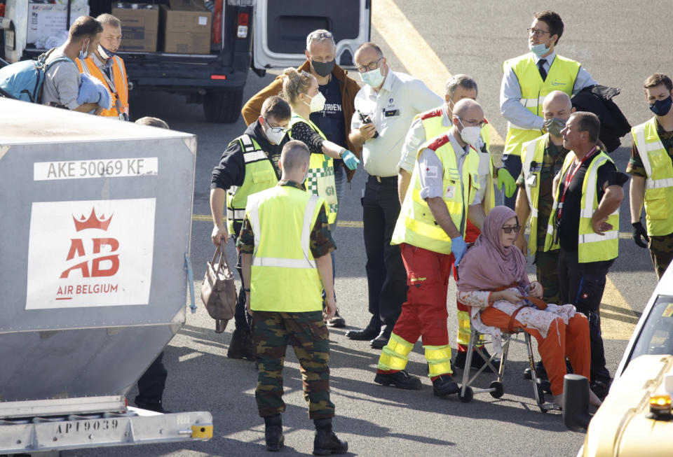 Medical personnel help a woman to disembark from a chartered plane, carrying people recently evacuated from Afghanistan, as it arrives at Melsbroek Military Airport in Melsbroek, Belgium, Wednesday, Aug. 25, 2021. (AP Photo/Olivier Matthys)