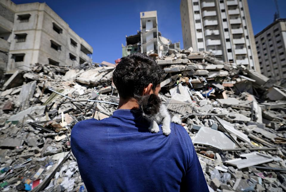 Ahmed Mosabeh, a 28-year-old Palestinian with special needs, holds one of several rescue kitten he cares for next to a destroyed building. He had evacuated his home earlier to a safer area due to Israeli air raids Tuesday in Gaza City. (Photo: MAHMUD HAMS/AFP via Getty Images)