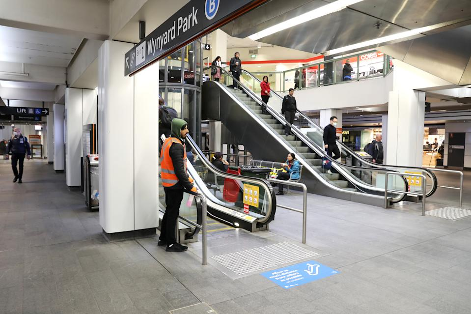SYDNEY, AUSTRALIA - MAY 25: A staff member cleans the handrail of an escalator at Wynyard station on May 25, 2020 in Sydney, Australia. Additional security and marshalling staff will be on hand at major Sydney transport hubs as schools return to regular full-time lessons and business reopen as New South Wales continues to relax COVID-19 restrictions. (Photo by Mark Kolbe/Getty Images)