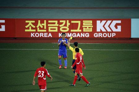 A player from the Philippines receives a yellow card in front of an advertising board while playing against North Korea in their team's preliminary 2018 World Cup and 2019 AFC Asian Cup qualifying soccer match at the Kim Il Sung Stadium in Pyongyang October 8, 2015.  REUTERS/Damir Sagolj/File Photo