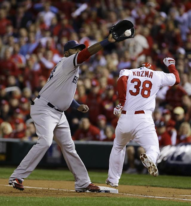 St. Louis Cardinals shortstop Pete Kozma is out at first on a bunt as Boston Red Sox designated hitter David Ortiz takes the through during the third inning of Game 5 of baseball's World Series Monday, Oct. 28, 2013, in St. Louis. (AP Photo/Matt Slocum)