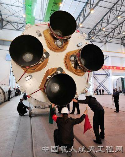 Staff members hoist the first-stage launcher of the Long March 2F rocket, which will carry China's new piloted spacecraft Shenzhou 10, at Jiuquan Satellite Launch Center.