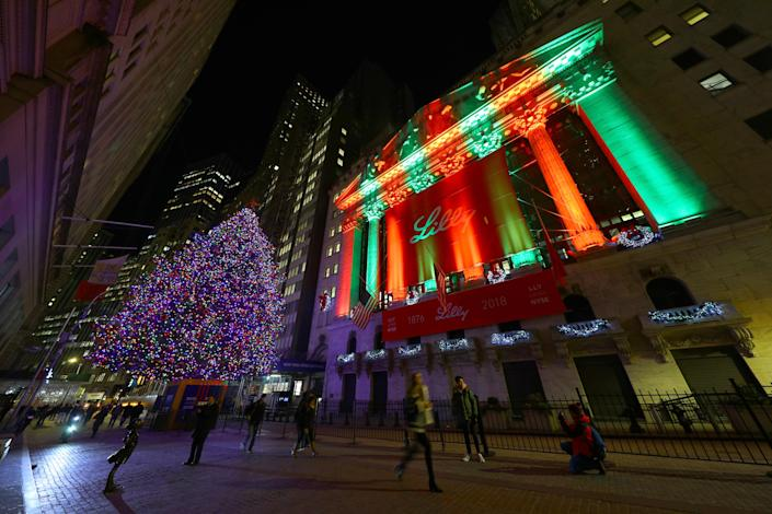Pedestrians walk past a Christmas tree on Broad Street and the seasonal lights illuminating the New York Stock Exchange. (Photo: Gordon Donovan/Yahoo News)