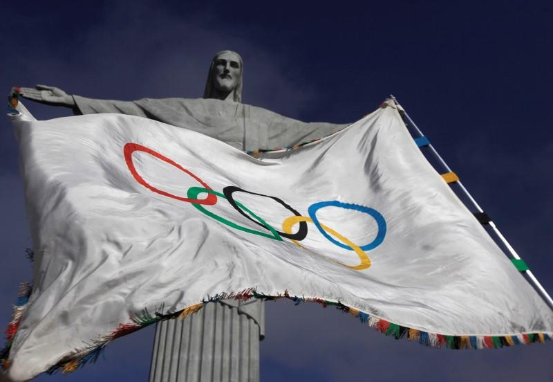"""The Olympic Flag flies in front of """"Christ the Redeemer"""" statue during a blessing ceremony in Rio de Janeiro"""