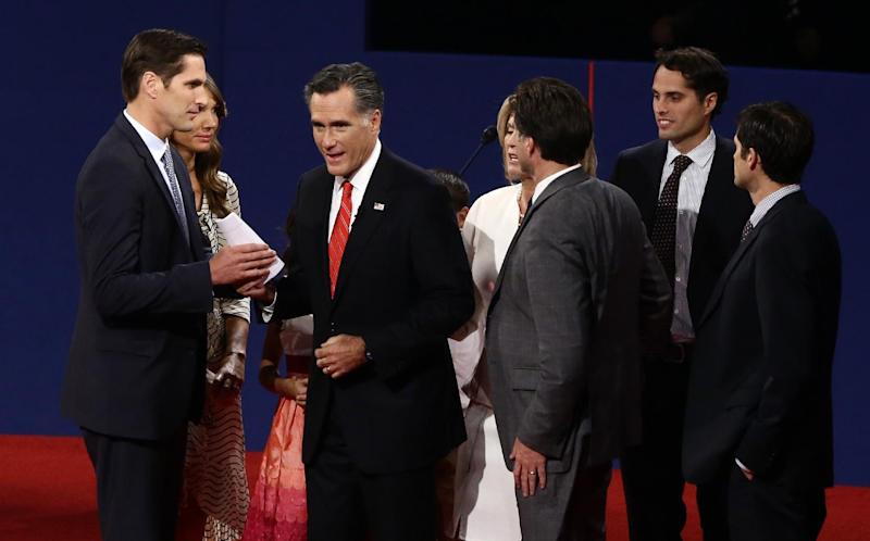 FILE - In this Oct. 3, 2012 file photo, Republican presidential candidate, former Massachusetts Gov. Mitt Romney hands papers to his son Josh, accompanied by family members, after he participated in the first presidential debate with President Barack Obama in Denver. Dozens of celebrities, elected officials, and others are blitzing through battleground states in the White House race's final days. Their goal: give the presidential campaigns a daily presence in key states even when the men at the top of the ticket (and their running mates) pitch for votes elsewhere.  (AP Photo/Charles Dharapak, File)