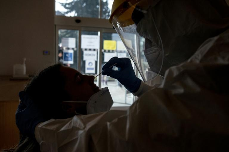 A Czech soldier wearing protective equipment (PPE) takes a sample from a patient at a coronavirus testing centre in Chodova Plana town, western Bohemia
