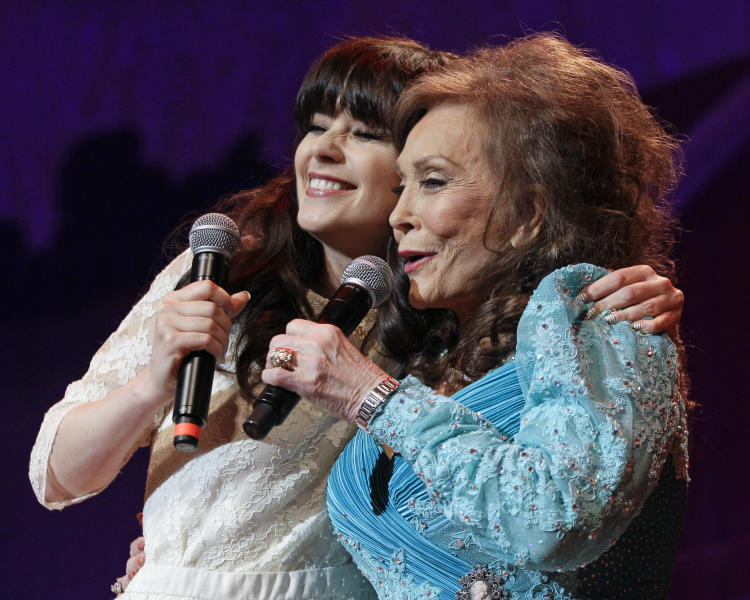"""Country music star Loretta Lynn, right, and actress Zooey Deschanel sing Lynn's hit """"Coal Miner's Daughter"""" during a performance of the Grand Ole Opry on Thursday, May 10, 2012, in Nashville, Tenn. During her appearance on the show, Lynn announced that a musical of """"Coal Miner's Daughter"""" is in development and Deschanel will play her. (AP Photo/Mark Humphrey)"""